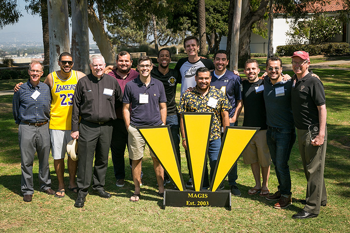 A group of alumni standing in front of a Magis sign